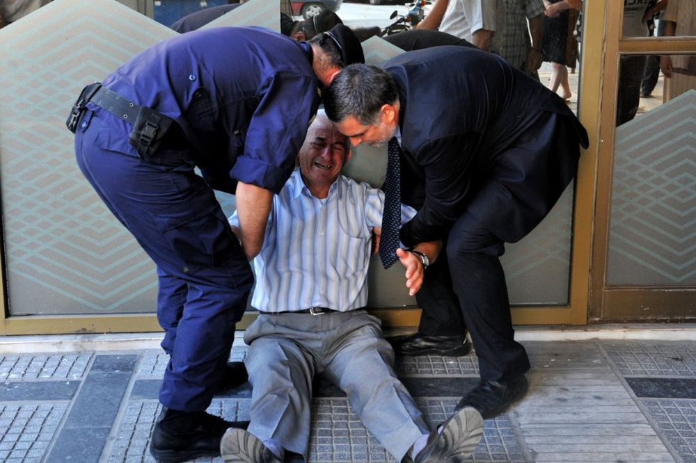 SLIKA GRČKE TRAGEDIJE OBIŠLA SVET: Policija tešila uplakanog penzionera, koji je ostao bez penzije
