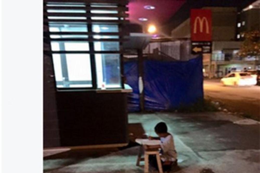 (FOTO) RADI DOMAĆI NA ULIČNOM SVETLU: Ovo je priča dečaka (9) sa fotografije koja je dirnula svet