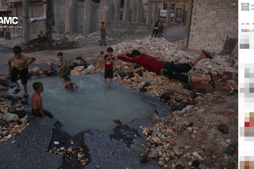 BRČKAJU SE OKRUŽENI SMRĆU: Deca u Alepu napravila bazen u krateru bombe